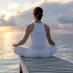 A woman meditates on a pier