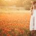 Girl in a poppy field with a retro camera
