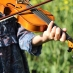 A woman plays a violin in a field