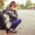 Sad boy sitting on the sidewalk