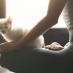 A cat on a woman's lap as she does yoga