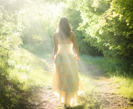 Woman in a white dress walking in the woods in sunlight