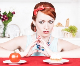 A woman choosing between a tomato and a cream cake