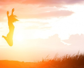 A woman jumping in front of a sunset