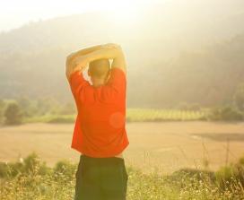 man in field stretching
