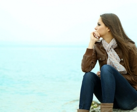 A worried woman gazes out to sea