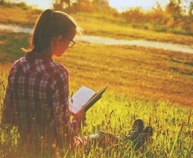 Girl reading a book outdoors