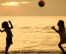 Kids playing ball on beach at sunset