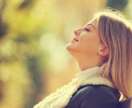 Happy woman facing sun outdoors