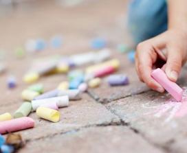 child drawing with chalk on sidewalk