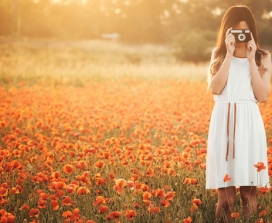 Girl in a poppy field with a retro camera