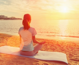 Woman on yoga mat looking at the ocean