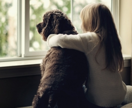 Girl with her dog looking out of a window