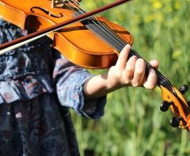 A woman plays a violin in a field