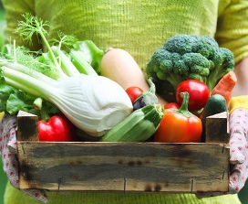 A woman holds a box of vegetables