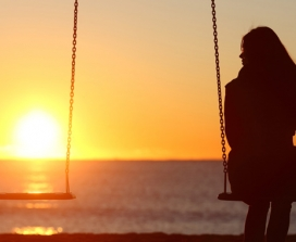 woman on swing at sunset